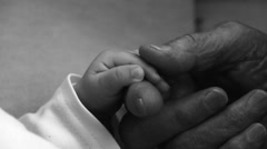 Hand in hand. Grandmother holds the hand of a newborn - stock footage