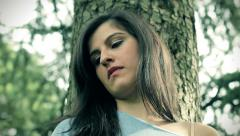Sad young woman standing by a tree - stock footage
