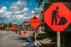 construction signs with road works in the background. - stock photo