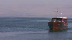 A boat bearing Christian pilgrims travels along the sea of Galilee in Israel. - stock footage