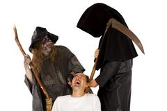 death and witch tug at victim - stock photo