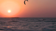Stock Video Footage of A windsurfer moves along a coastline at sunset.