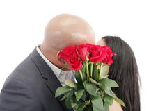 Two young dates kissing behind a bouquet of red roses Stock Photos