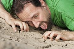 thirsty man on parched soil - stock photo