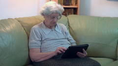 Old woman using a tablet computer, typing, granny playing games Stock Footage