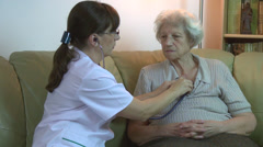 Home health care doctor & old female patient, checking heart rate Stock Footage