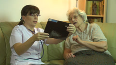 Home health care doctor & worried old woman patient discussing about Xray - stock footage
