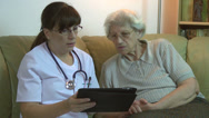 Stock Video Footage of Home health care doctor & old patient discussing about medical exam, tablet