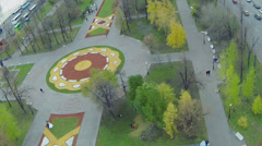 People walk near colorful flowerbeds in park of Bolotnaya square - stock footage