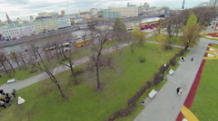People walk near colorful flowerbeds in park of Bolotnaya square Stock Footage