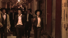 Hassidic Jews walk in the Arab Quarter of the old city of Jerusalem at night. Stock Footage
