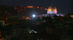 The Dome of the Rock towers over the Old City of Jerusalem at night. - stock footage