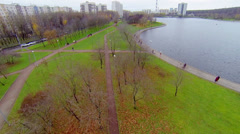 People walk by paths in park near Golyanovsky pond at autumn day Stock Footage