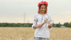 Young Girl in Ukrainian Costume with Bunch of Wheat Ears in Wheat Field HD Stock Footage