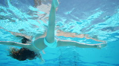 Little girl floating in the blue pool, view around under water Stock Footage