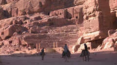 People ride donkeys near the ancient amphitheater in the ancient Nabatean ruins Stock Footage