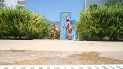 Mother with two daughters having fun with water near the pool Stock Footage