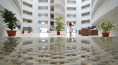 Children playing in the lobby of a grand hotel near the entrance Stock Footage
