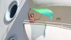 Girl waving kerchief on the balcony of the room at the hotel - stock footage