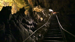 Young woman goes upstairs to exit from underground cave Stock Footage