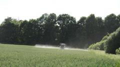 Tractor fertilize spray wheat crop plant field near forest Stock Footage