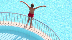 Boy sunbathes on separating ledge and then jumps into water Stock Footage