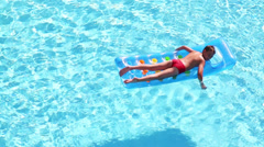 Boy floats in pool on sunny day lying at air mattress - stock footage