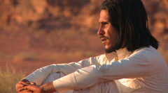 A Bedouin man sits and contemplates the desert. Stock Footage