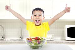 Pleased child with salad Stock Photos