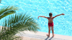 Boy takes sunbathe on edge of pool and then jumps into water Stock Footage