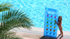 Little girl stands with inflatable mattress on edge of pool Stock Footage