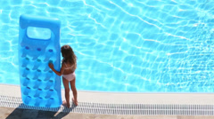 Little girl stands with inflatable mattress at poolside Stock Footage