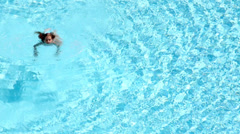Little girl swims in blue clear water of swimming pool Stock Footage
