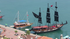 Ship with black pirate sails and boats docked at berth Stock Footage