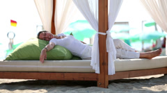 Woman lies in shadow of canopy on bed with wooden frame Stock Footage