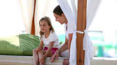 Mother and daughter sit on bed with wooden frame Stock Footage