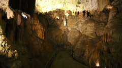 Walkway with fencing leading down to underground cave Stock Footage