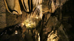 Descent into underground cave with stalactites and stalagmites - stock footage