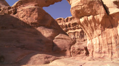 Tilt up to an amazing arch formation in the Sadi desert in Wadi Rum, Jordan with Stock Footage
