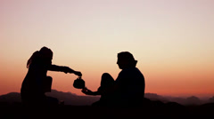 A Bedouin man pours tea and toasts a Western tourist in a silhouette shot. Stock Footage