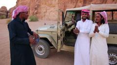 Three Bedouin men sing songs near their jeep in the Saudi desert of Wadi Rum, - stock footage