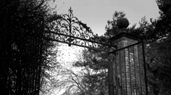 B & W old mansion gate with trees & leaves in wind - dolly shot - stock footage