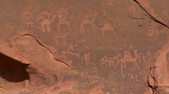 Ancient and mysterious petroglyphs depict humans and camels in the Saudi desert Stock Footage