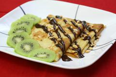 French crepes with chocolate and kiwi fruit Stock Photos