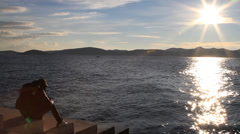 Man sitting and thinking by sea organ in Zadar Stock Footage