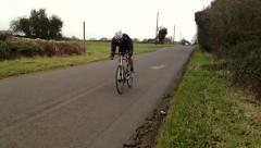 Road bike past fast RL downhil twds cam Stock Footage