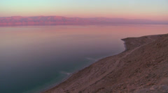 Pink and purple hues along the shoreline of the Dead Sea in Israel at dusk. - stock footage