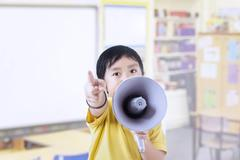 Boy in class using megaphone Stock Photos