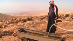 A Bedouin provides precious water for his flocks in the dry desert mountains of Stock Footage