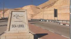 A road passes a sign indicating Sea Level near the Dead Sea in Israel. - stock footage